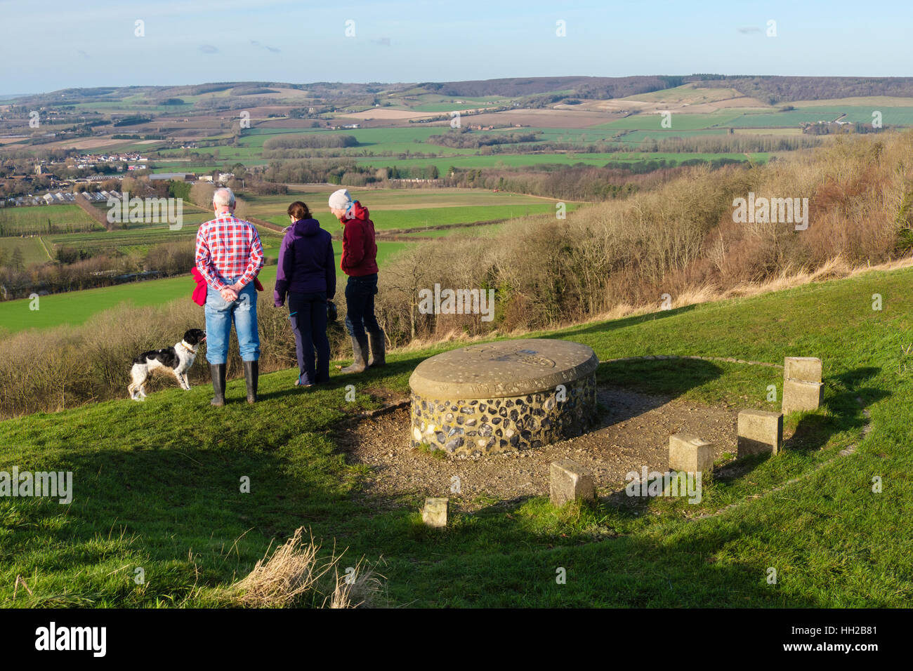 People looking at view by Wye Crown Millennium stone in Wye National Nature Reserve in hills on North Downs Way - Stock Image