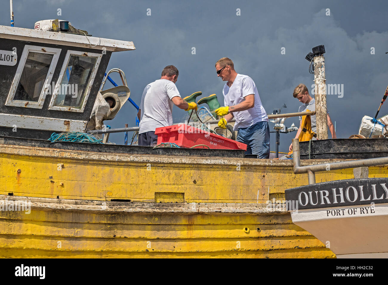 Cleaning Up The Fishing Boats On The Beach Hastings UK - Stock Image