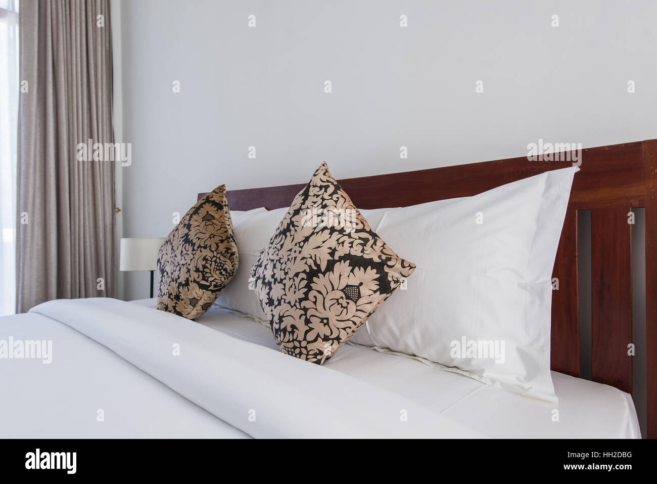 square brown pillows on a double bed in bedroom - Stock Image