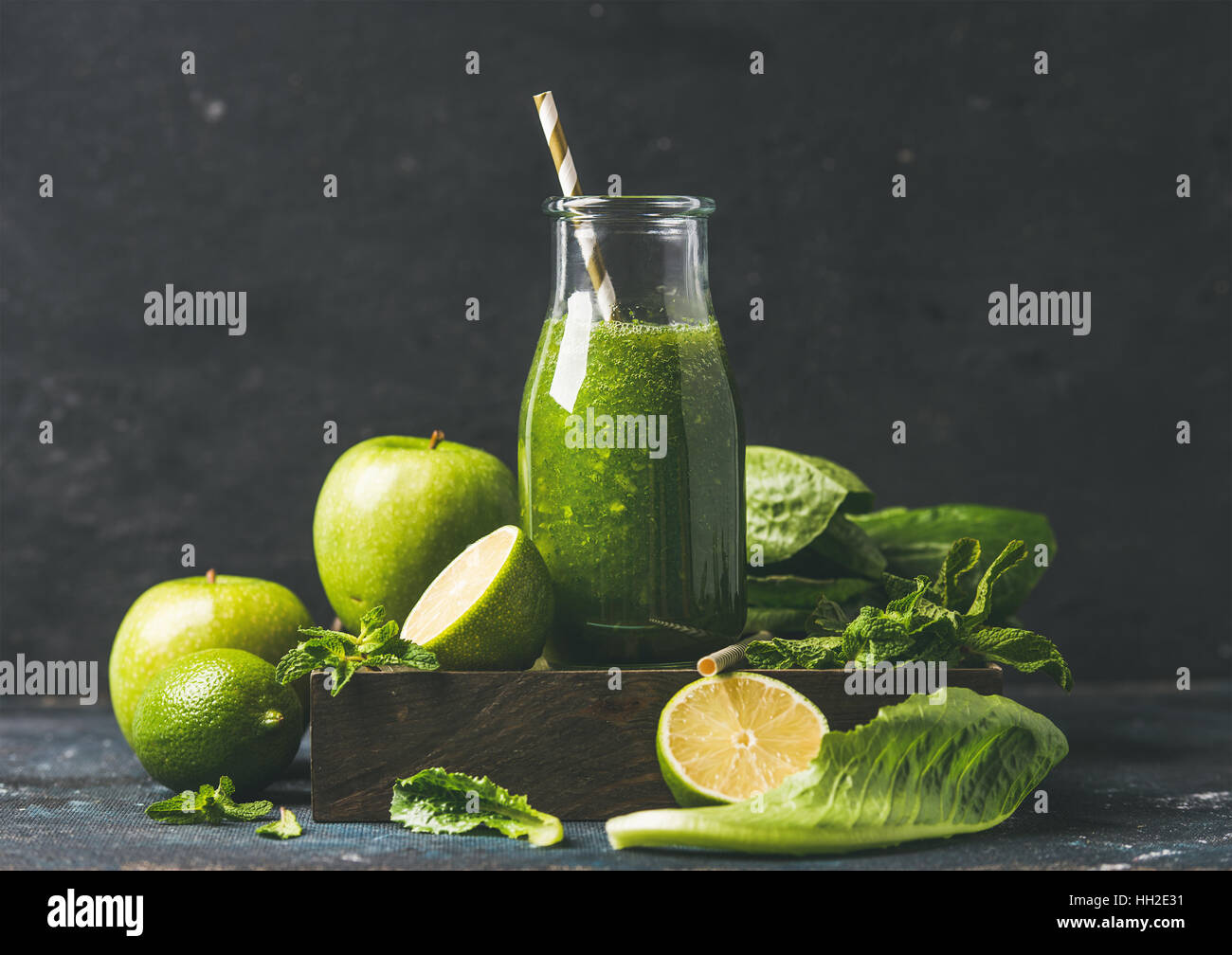 Green smoothie in glass bottle with apple, romaine lettuce, lime Stock Photo