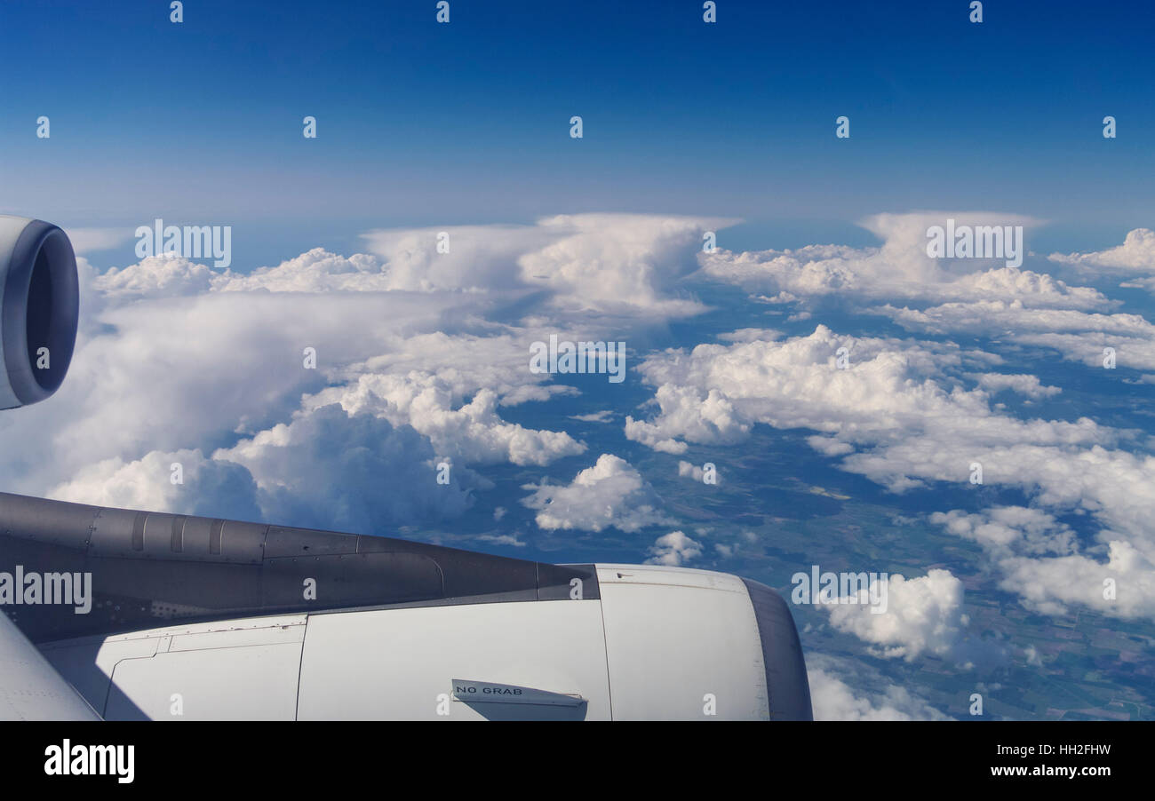 View out of an airplane over a row of anvil-shaped cumulonimbus clouds. Stock Photo