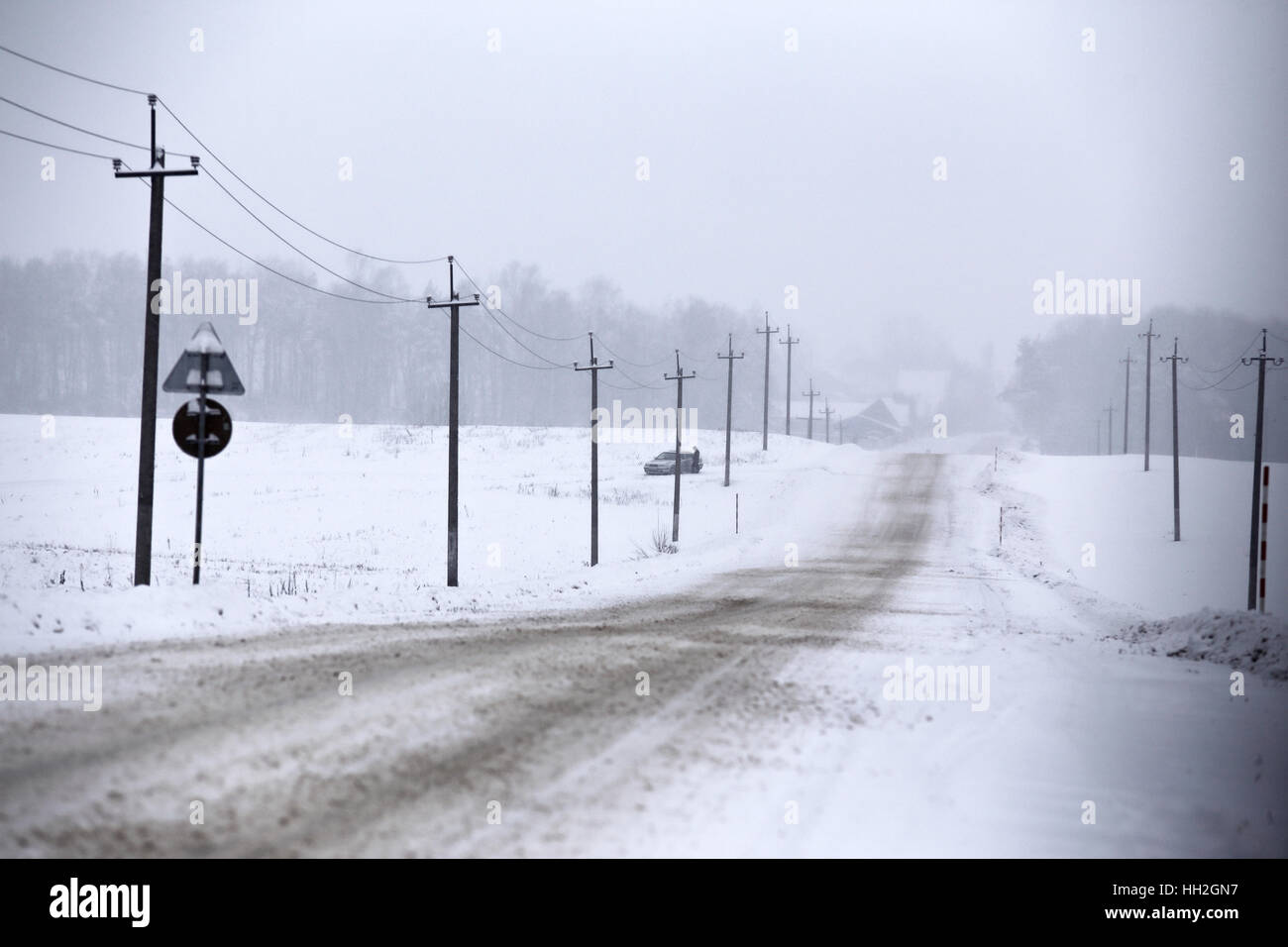 Snowfall and sleet on winter road. Ice snowy road. Winter snowstorm. Black ice and blizzard. - Stock Image