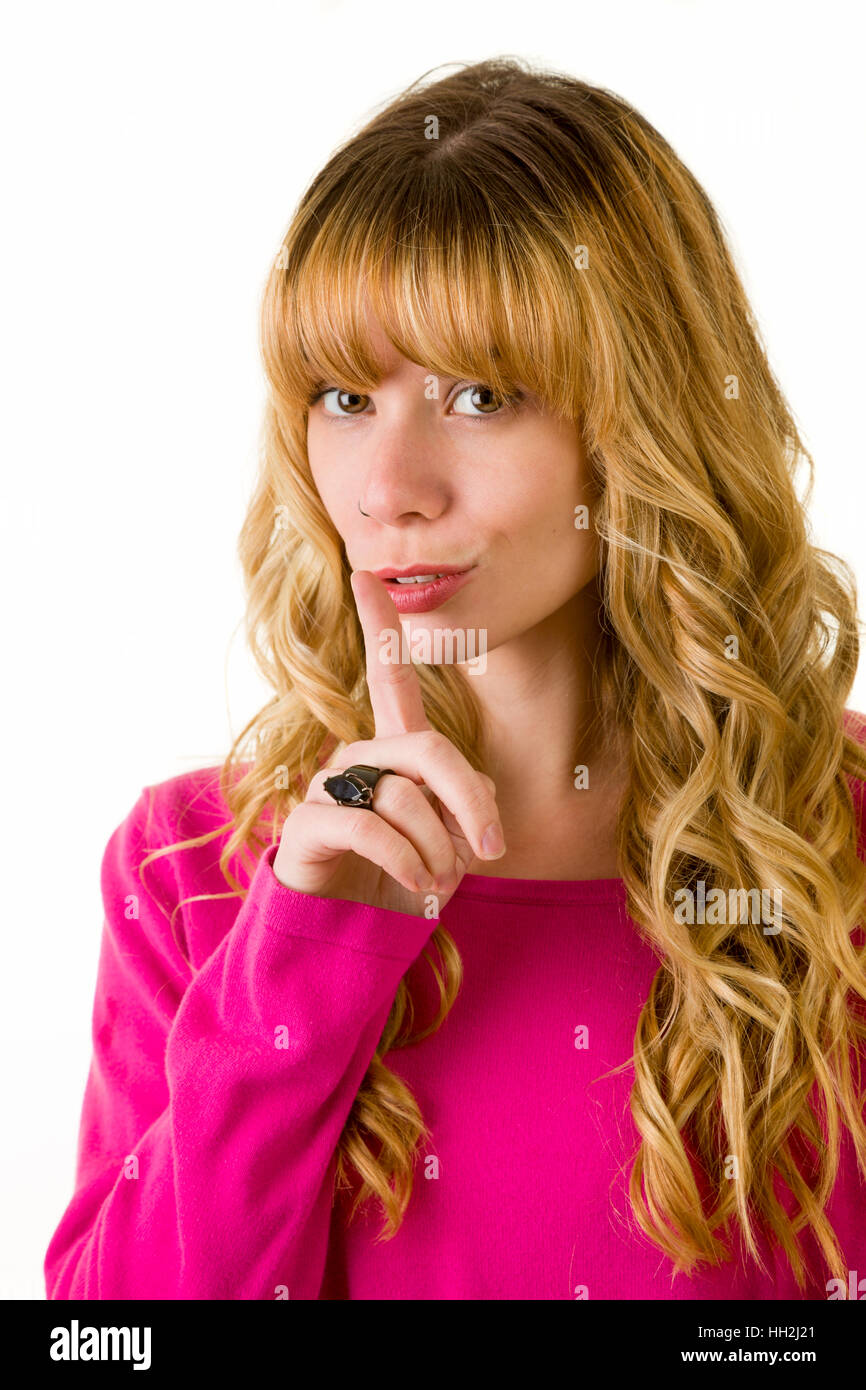 Attractive blonde woman covering her mouth. Quiet please. - Stock Image