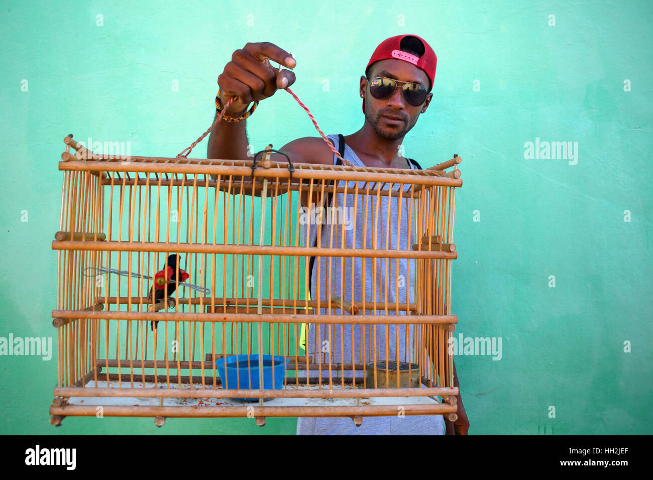 Portrait of cuban man carrying a cage with bird inside in Trinidad, Cuba - Stock Image
