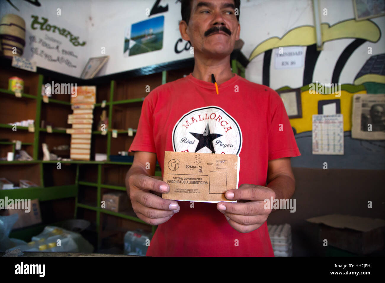 A man is showing a «Libreta de Abastecimiento» («Supplies booklet») in a grocery store in Trinidad. - Stock Image