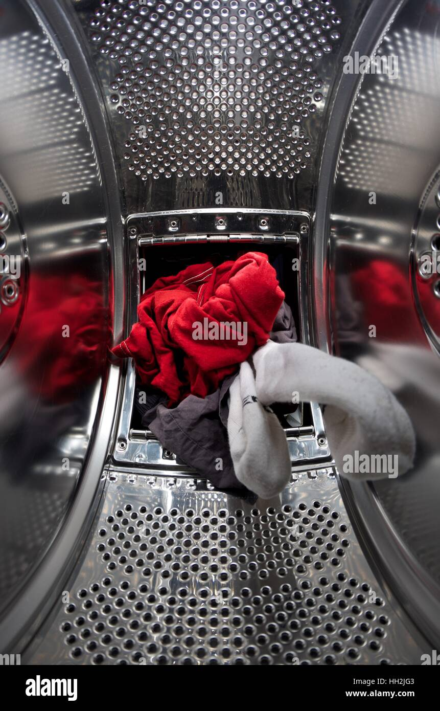 Laundry being loaded into a top loading washing machine - Stock Image