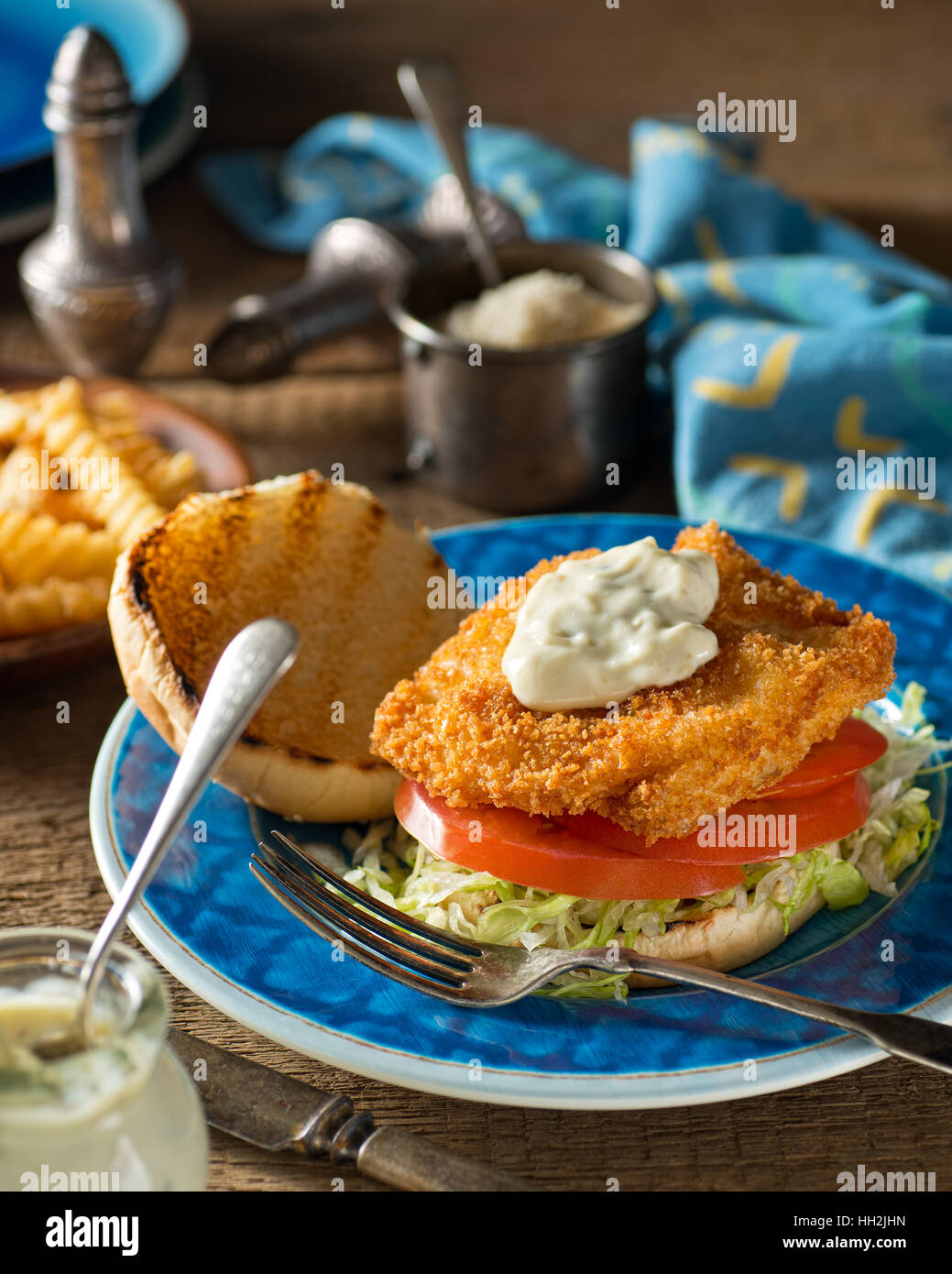 A delicious home made fish burger with lettuce, tomato, and tartar sauce. - Stock Image