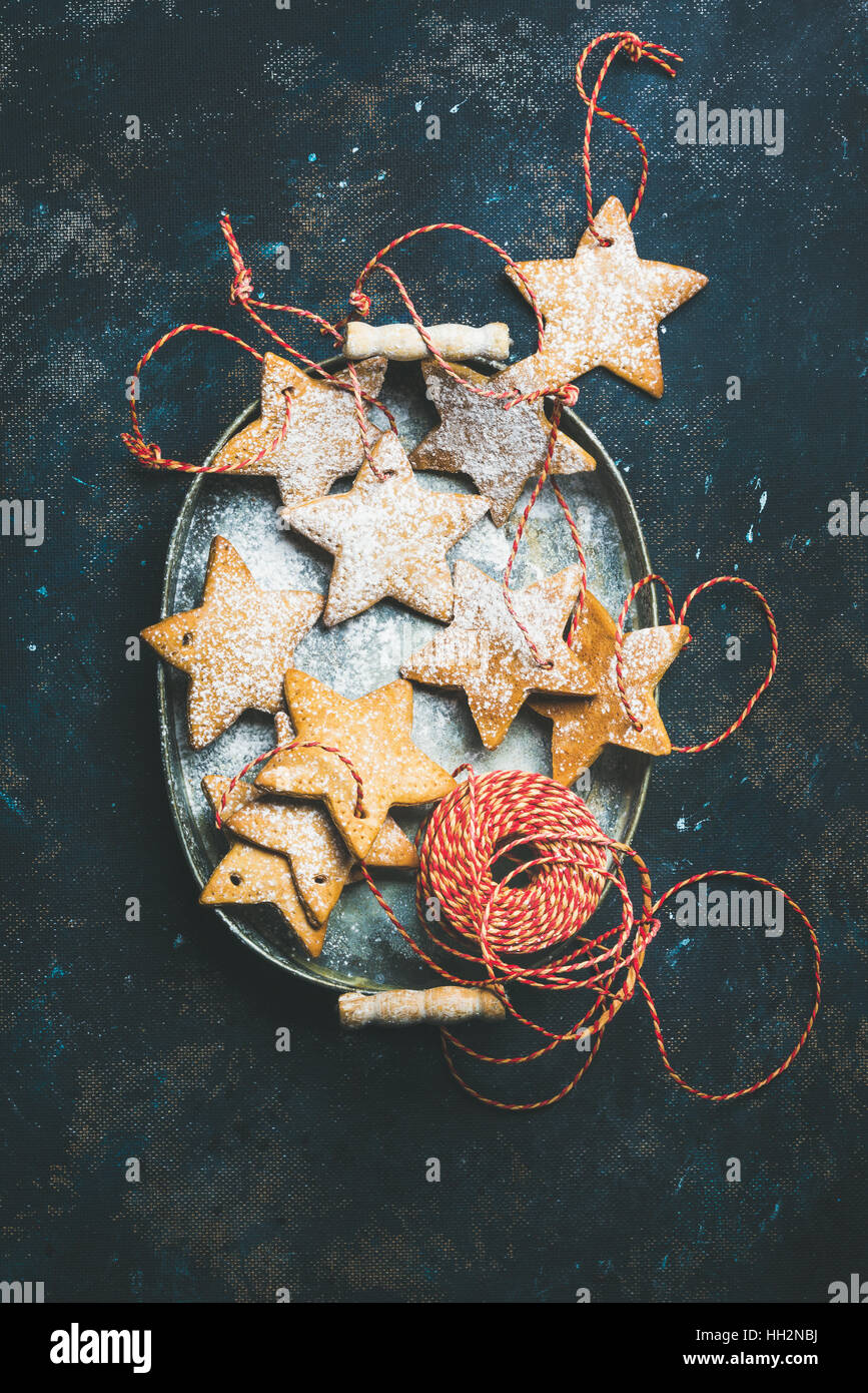 Christmas holiday star shaped gingerbread cookies over dark blue background - Stock Image