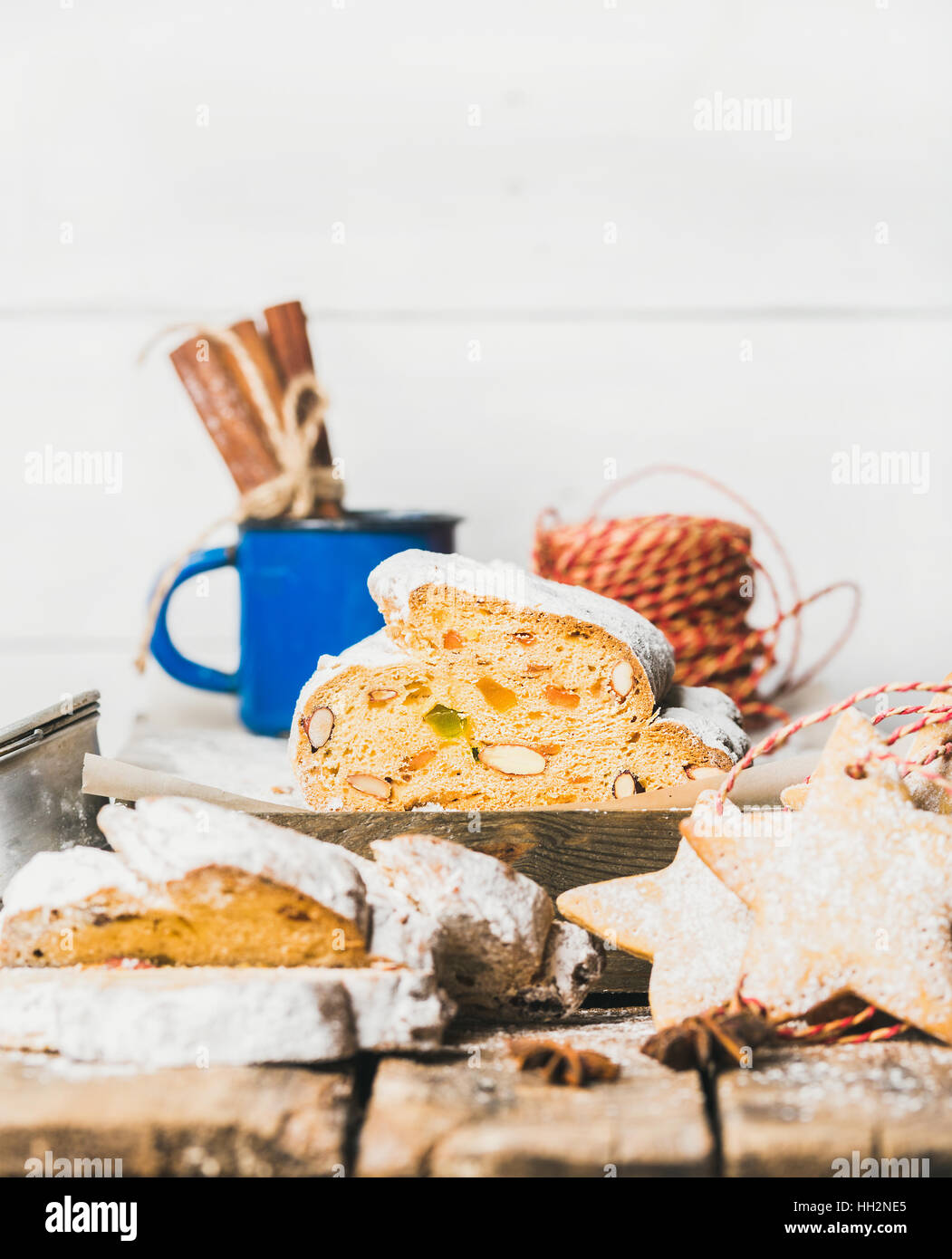 Traditional German Christmas cake Stollen with gingerbread cookies, white background - Stock Image