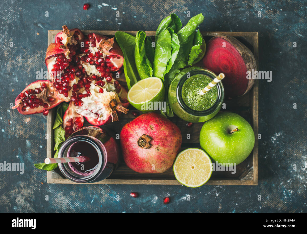 Green, purple fresh juices with fruit, greens, vegetables in tray - Stock Image