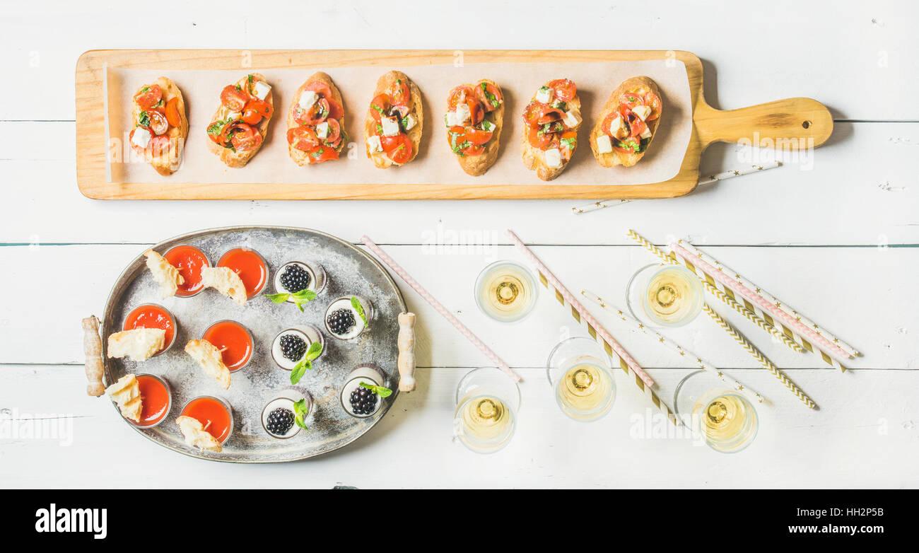Brushettas, gazpacho shots, desserts, champagne and straws over white background - Stock Image