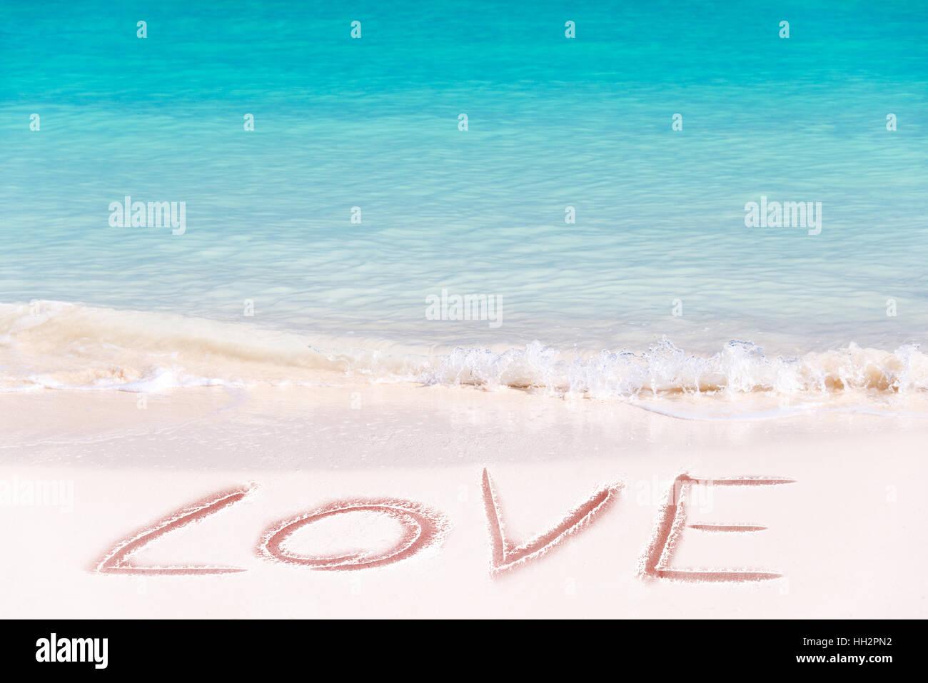 Love written on the white sand of an idyllic beach Stock Photo