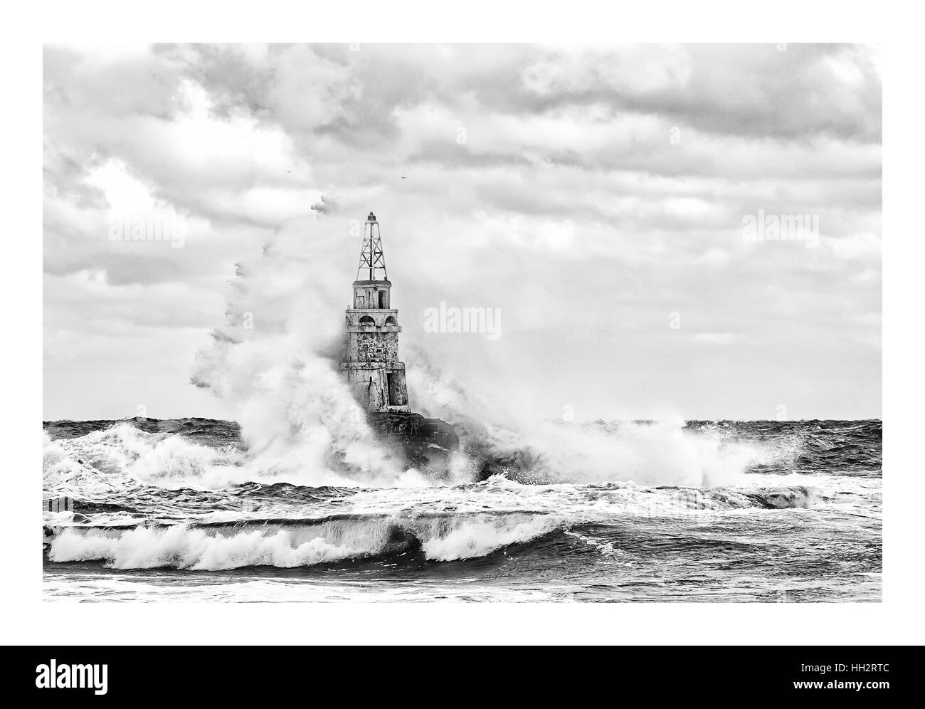 Stormy cloudy day. Dramatic sky and huge waves at the Lighthouse - Stock Image