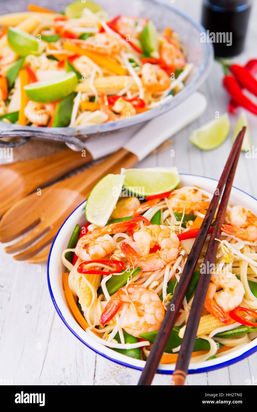 A healthy stir-fry of shrimp and vegetables served over noodles. - Stock Image