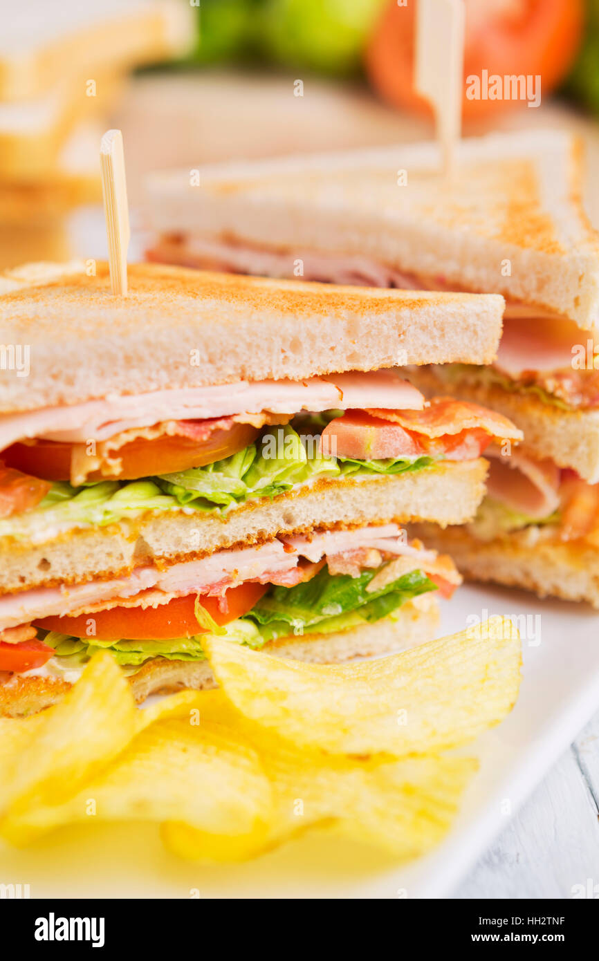 A club sandwich on a rustic table in bright light. - Stock Image