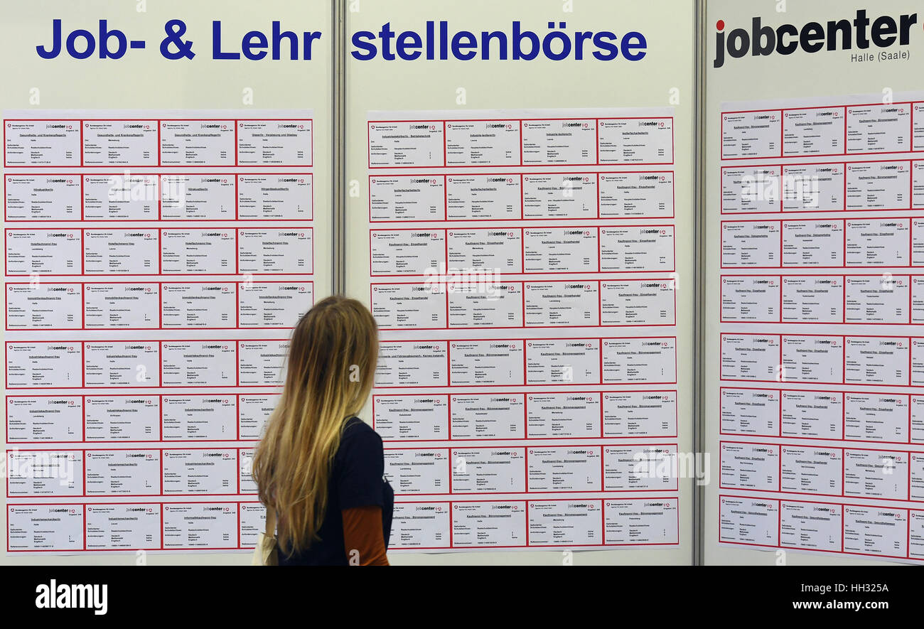 A young woman looking at a baord of job and apprenticeship ads at the start of the Chance 2017 careers fair in Halle/Saale, - Stock Image