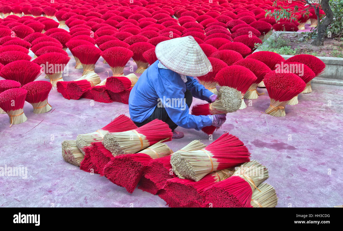 Worker bundling preparing red bamboo sticks for incense application. - Stock Image