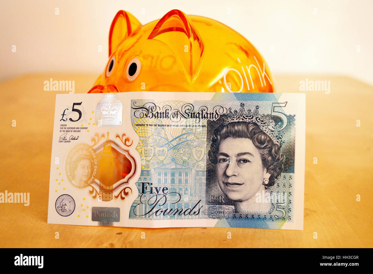 Front of the new polymer UK five pound note leaning against an orange piggy bank. - Stock Image