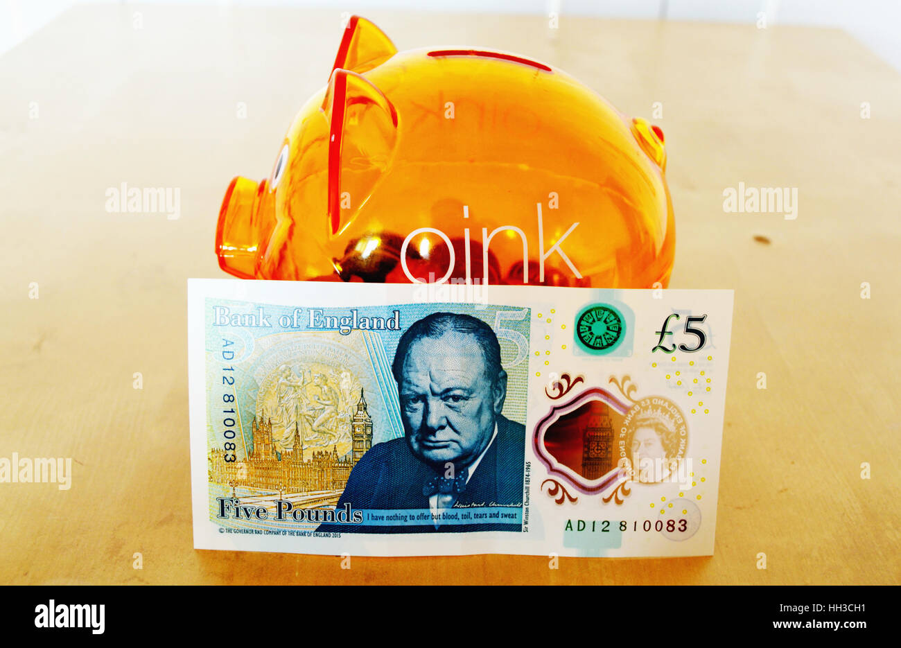 Back of the new polymer UK five pound note leaning against an orange piggy bank - Stock Image