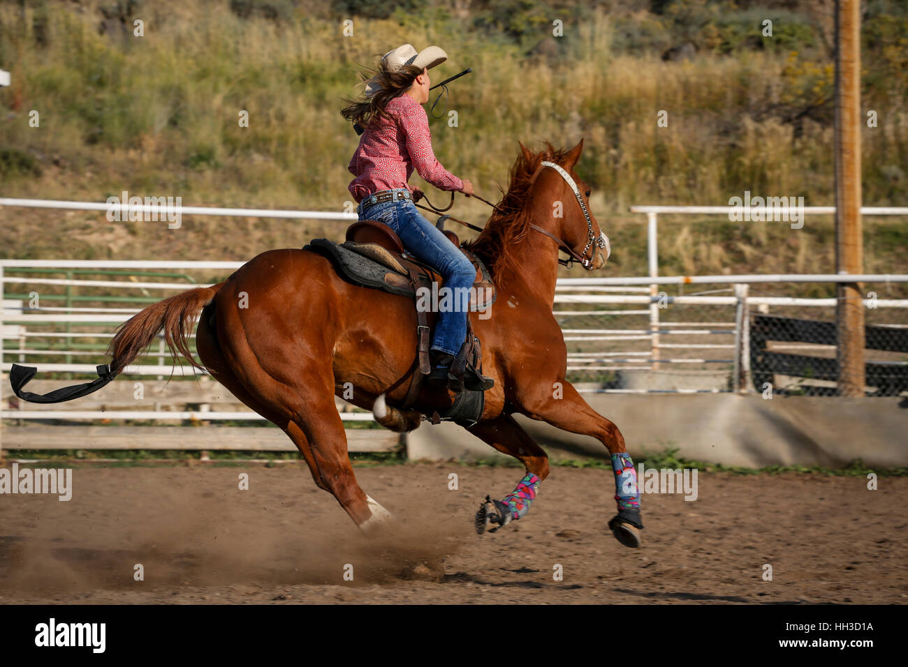 Young woman riding a horse through a rodeo arena during a youth rodeo event. - Stock Image