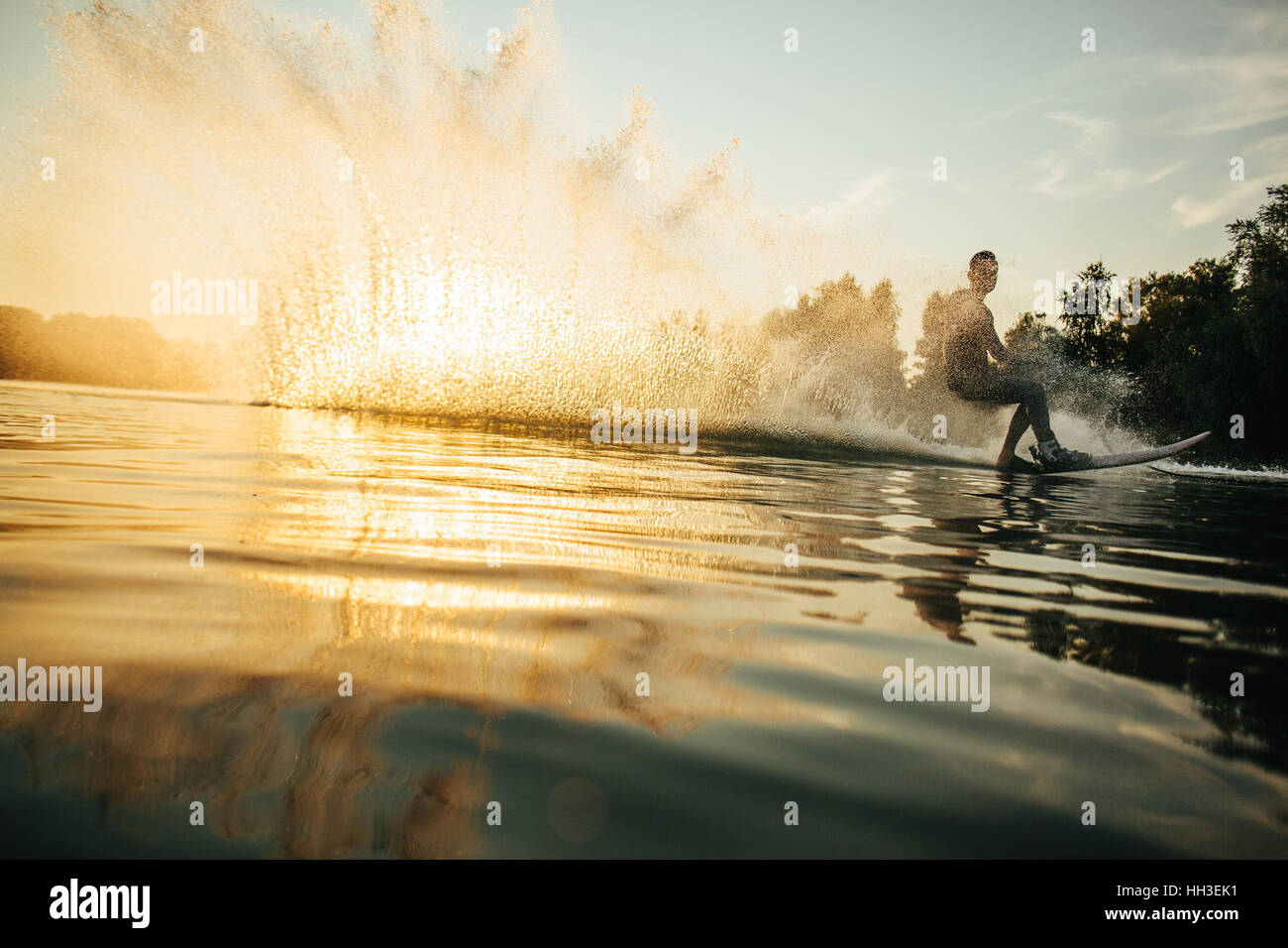 Low angle shot of man wakeboarding on a lake. Man water skiing at sunset. - Stock Image