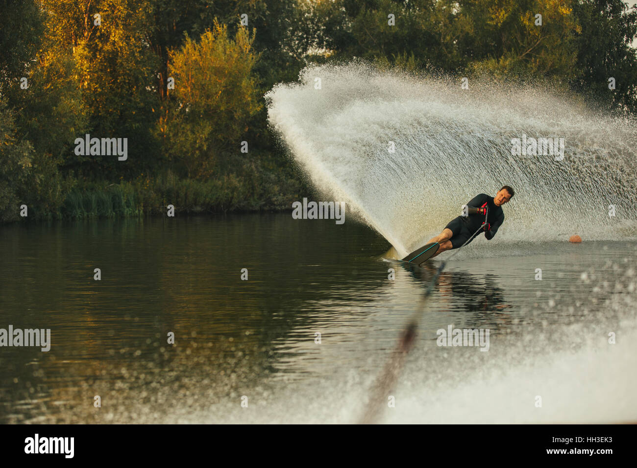 Wakeboarder skiing on lake with splash of water. Man practicing wakeboarding stunts. - Stock Image