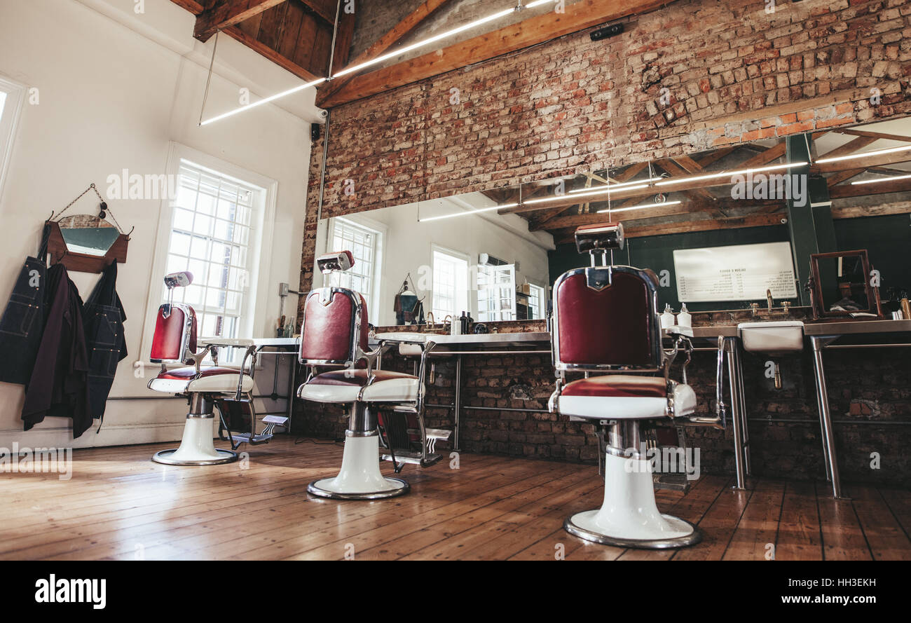 Horizontal shot of empty chairs in retro styled barbershop. Hair salon interior. - Stock Image