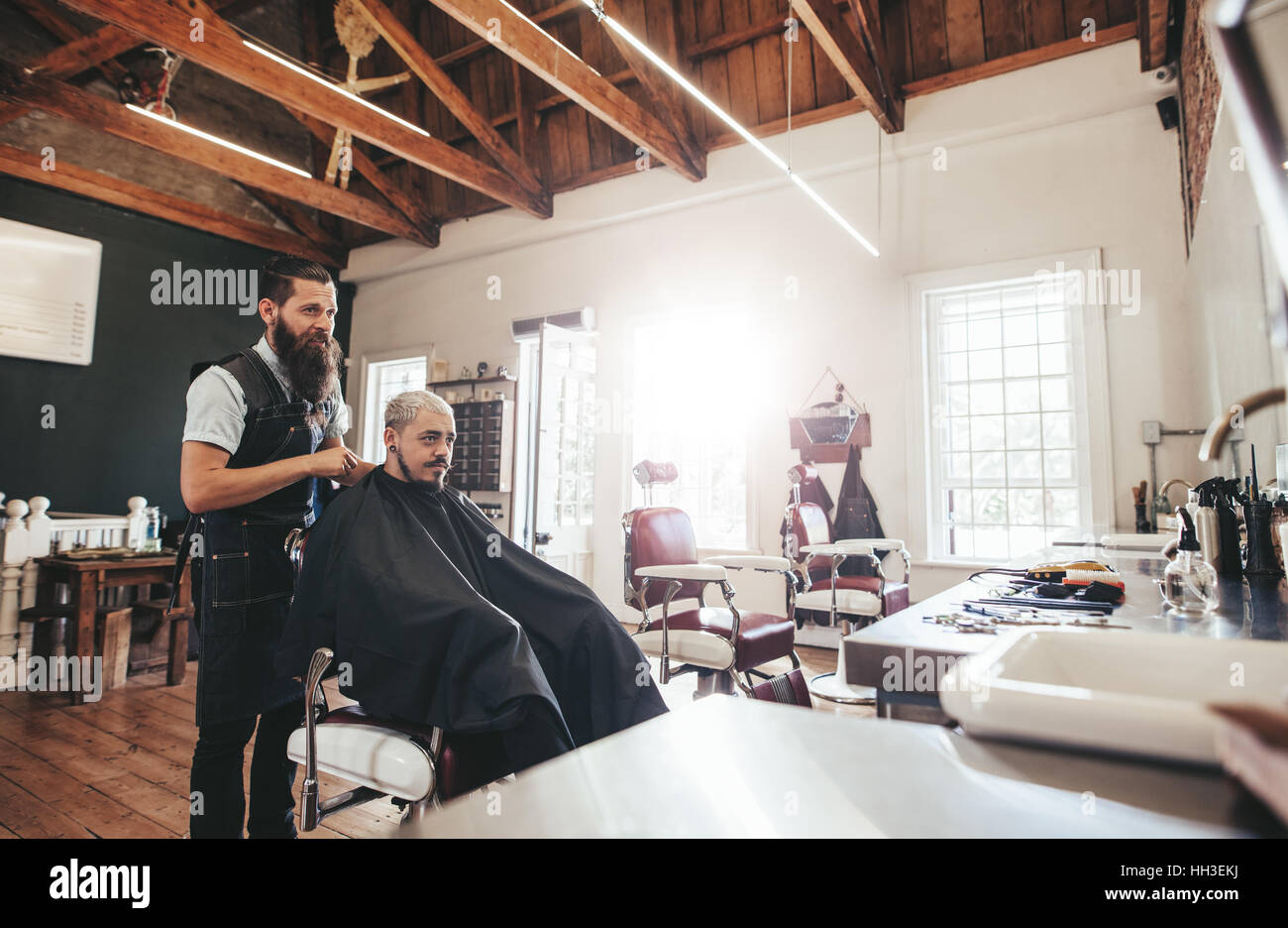 Young man getting haircut at barber shop. Hairdresser with customer at salon. - Stock Image