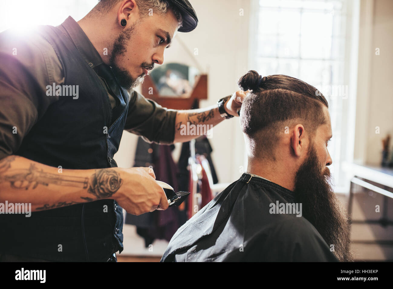 Stylish hairdresser cutting hair of client at barber shop. Beard man getting haircut at salon. - Stock Image