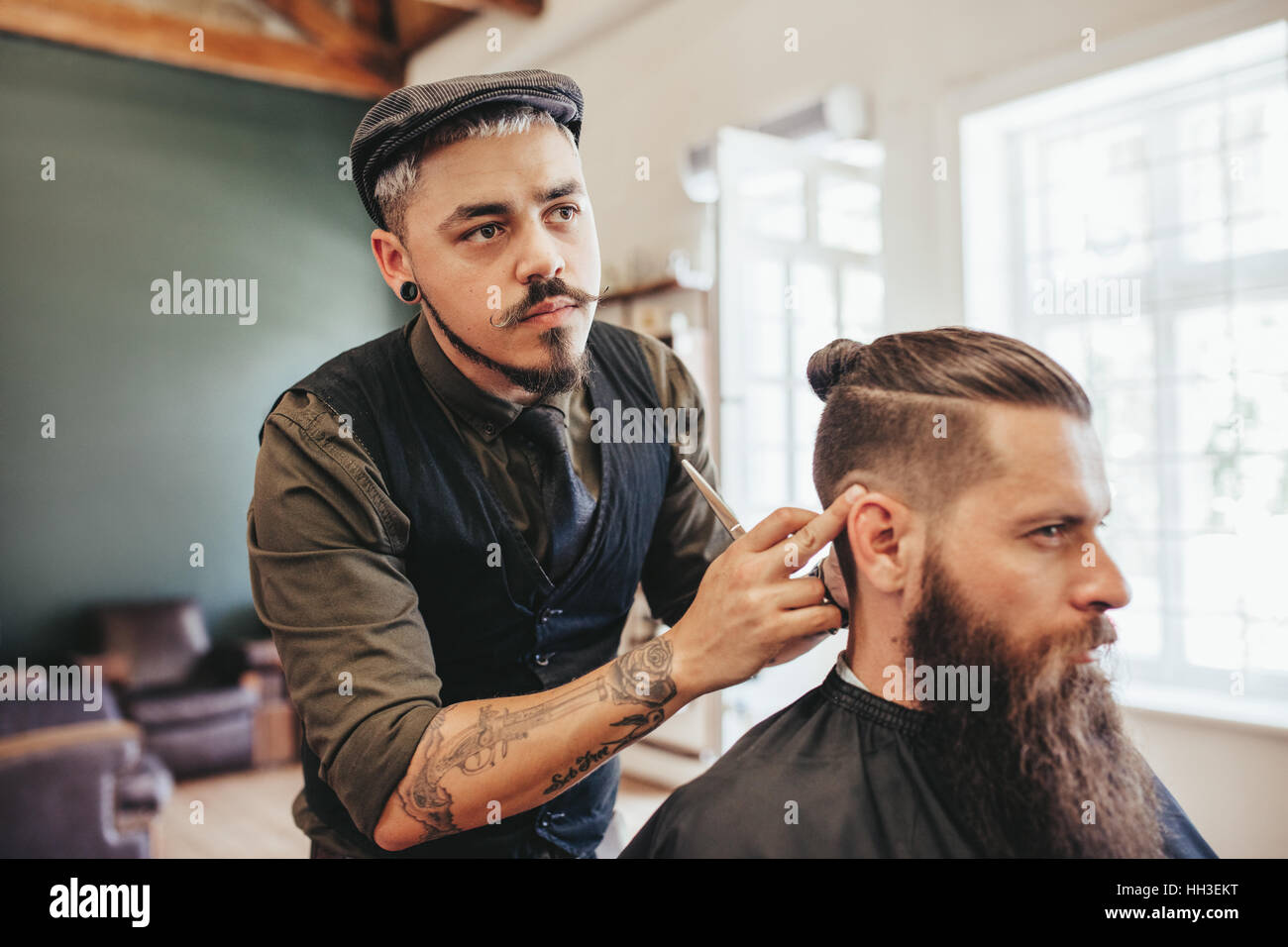 Hairdresser checking symmetry of haircut of his client at barbershop. Bearded man getting haircut by barber at barbershop - Stock Image