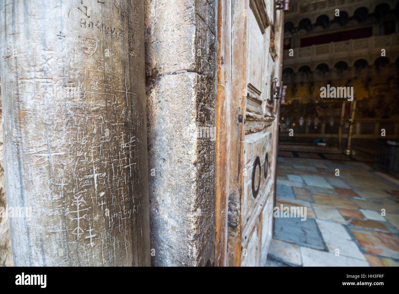 Marble pillars and old wooden door at the entrance to the Church of the Holy Sepulchre in Jerusalem, Israel Stock Photo