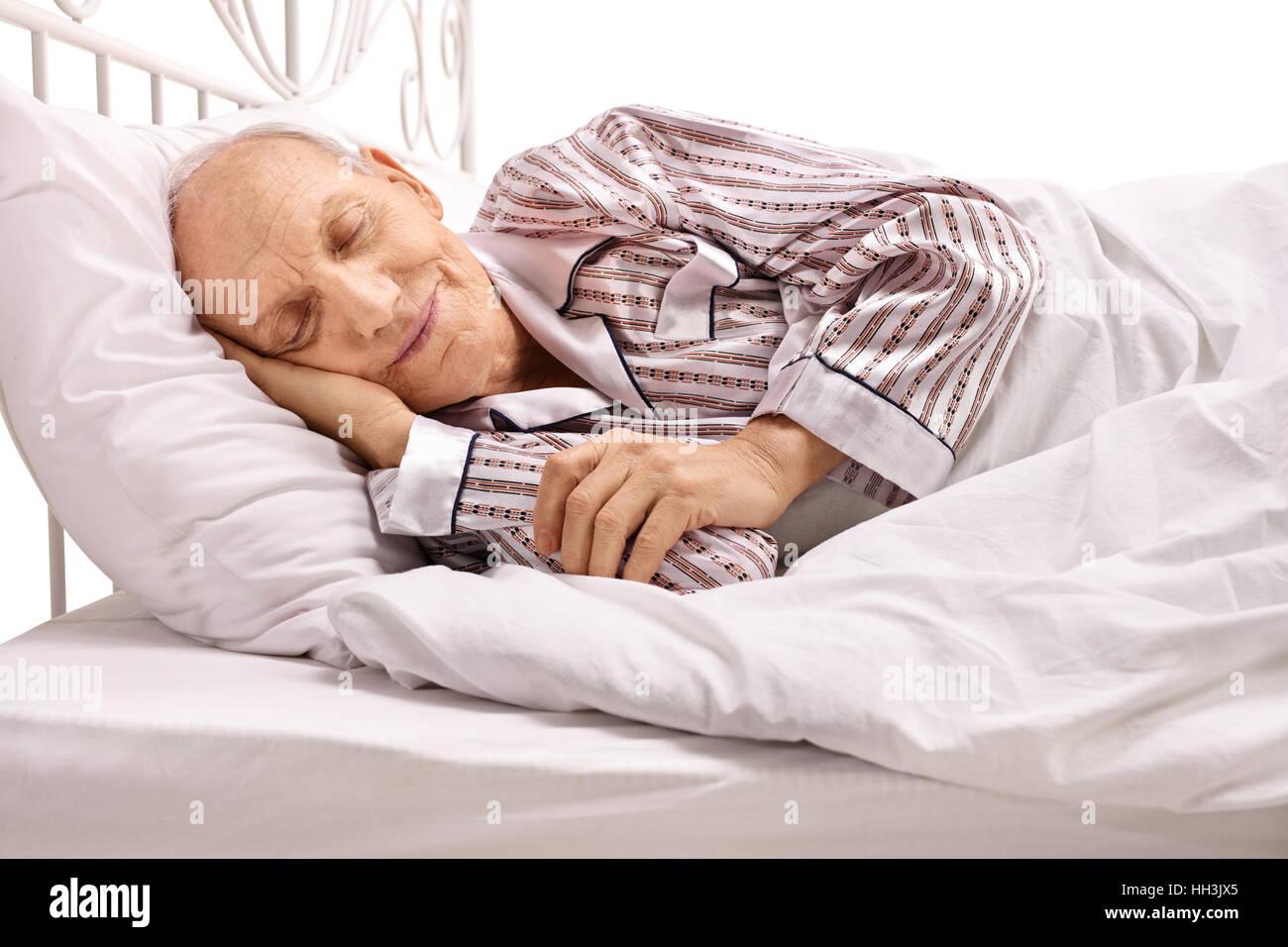 Senior sleeping in bed isolated on white background - Stock Image