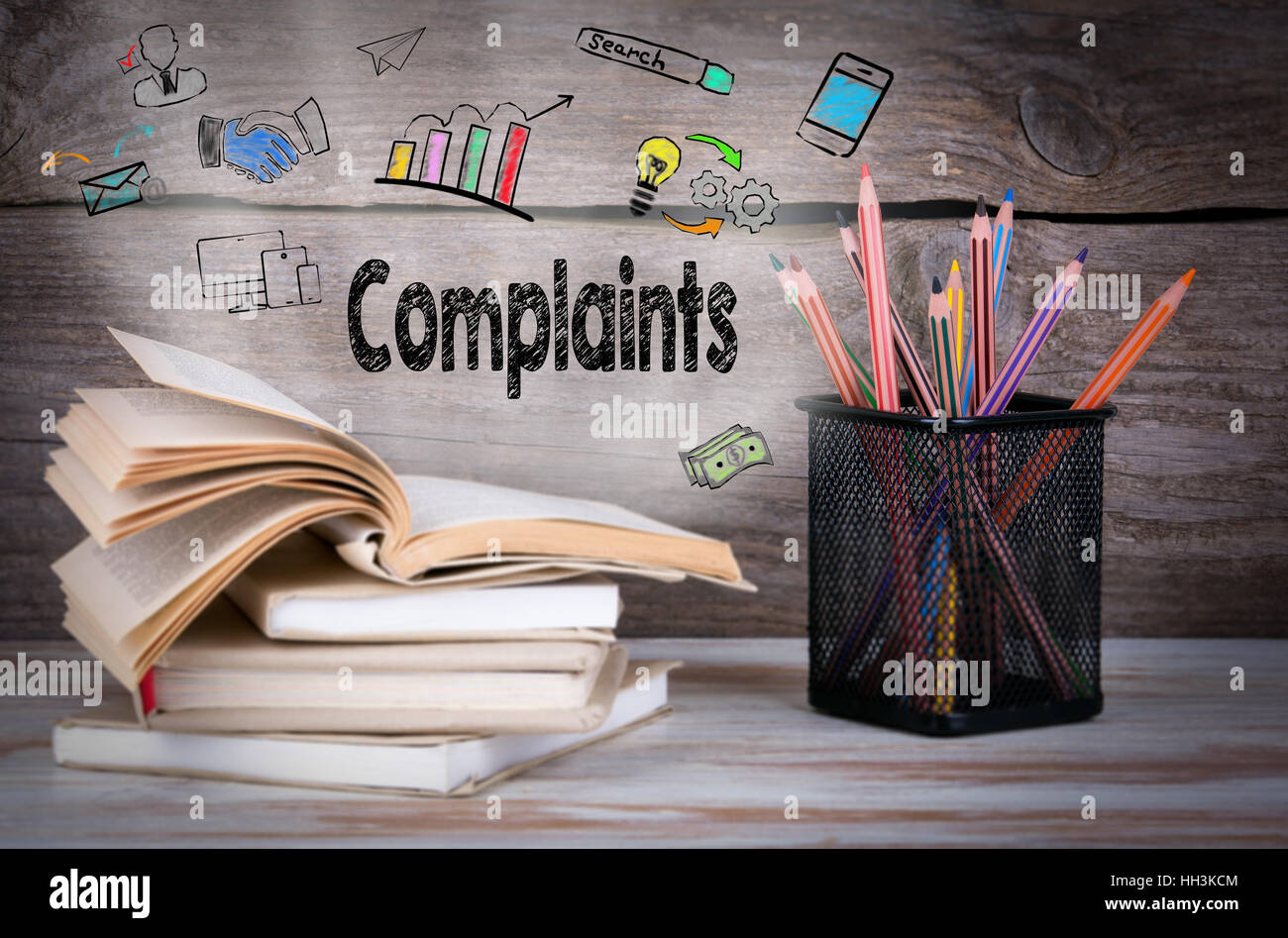 Complaints, Business Concept. Stack of books and pencils on the wooden table. - Stock Image