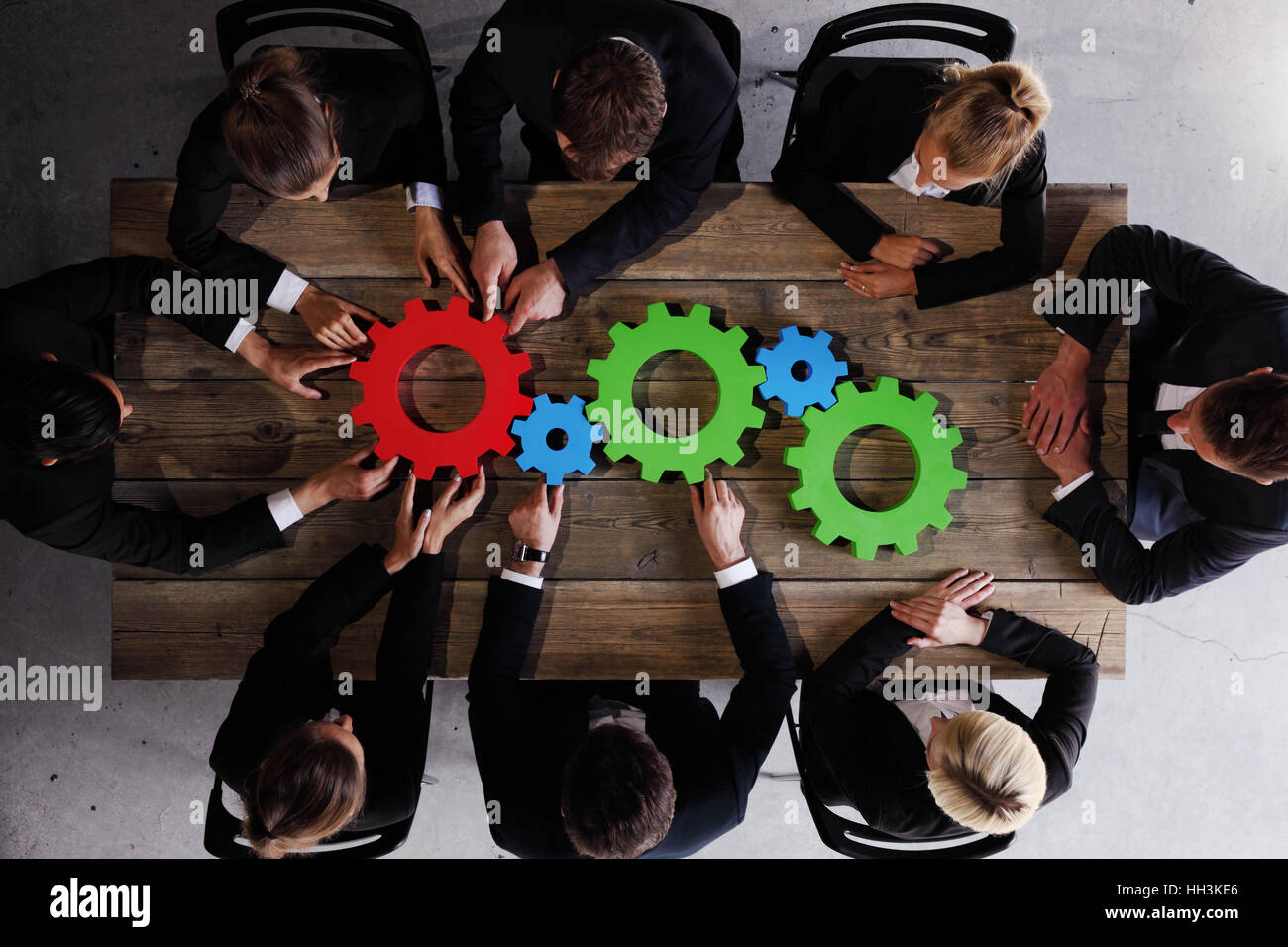Group of business people seen from above gathering cogs of business sitting together around the table - Stock Image