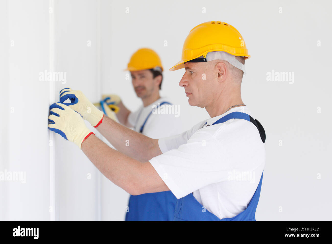 Men in uniform and hardhats measuring wall with tape - Stock Image