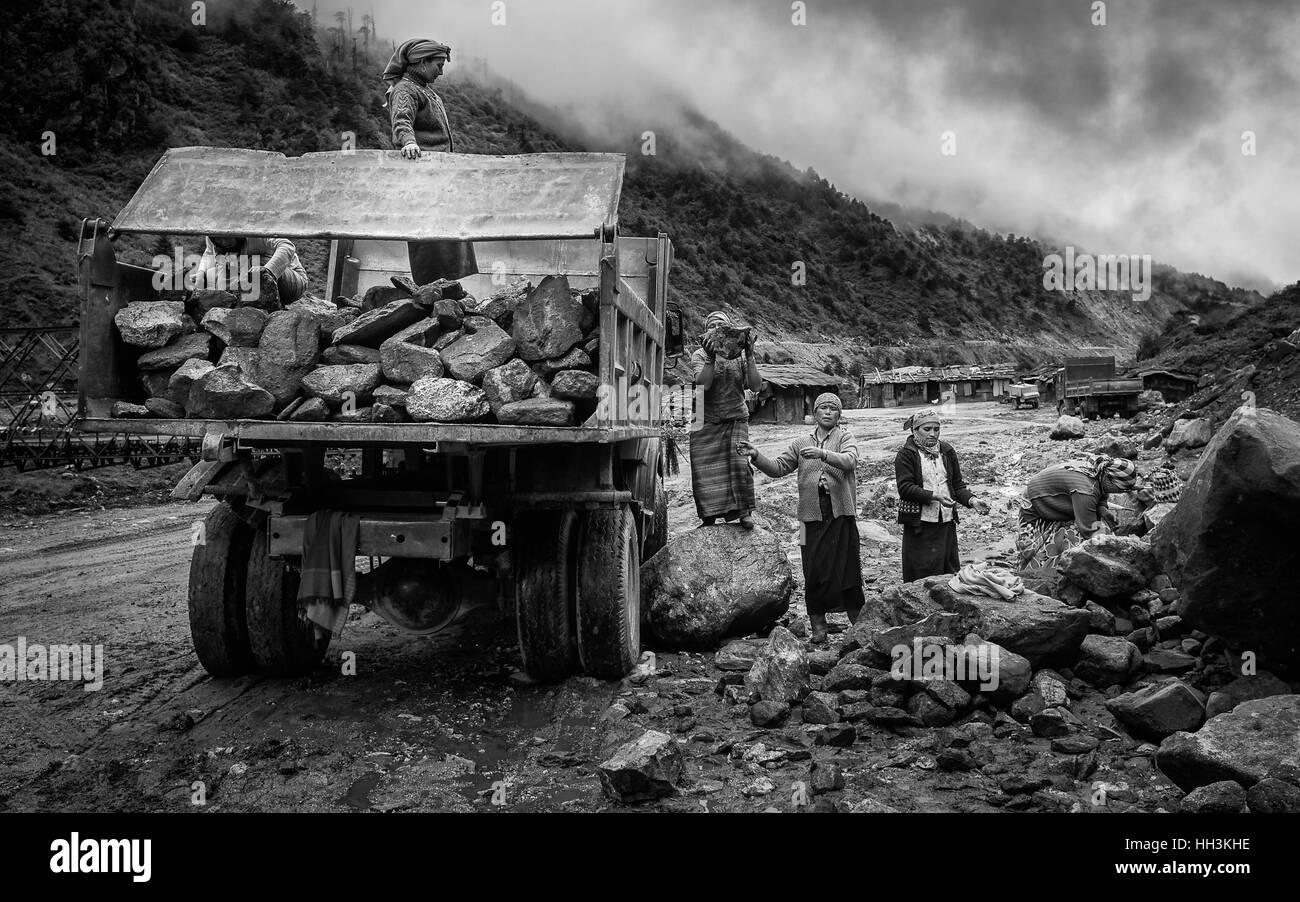 A team of women construction workers clear a landslide of boulders and rocks from road under construction in Himalayas. - Stock Image