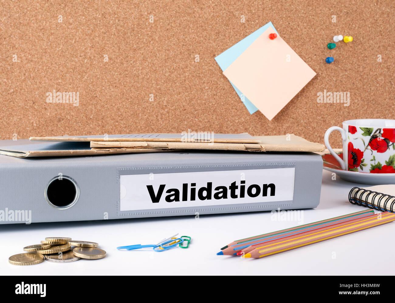 Validation. Folder on office desk. Money, Coffee Mug and colored pencils. - Stock Image