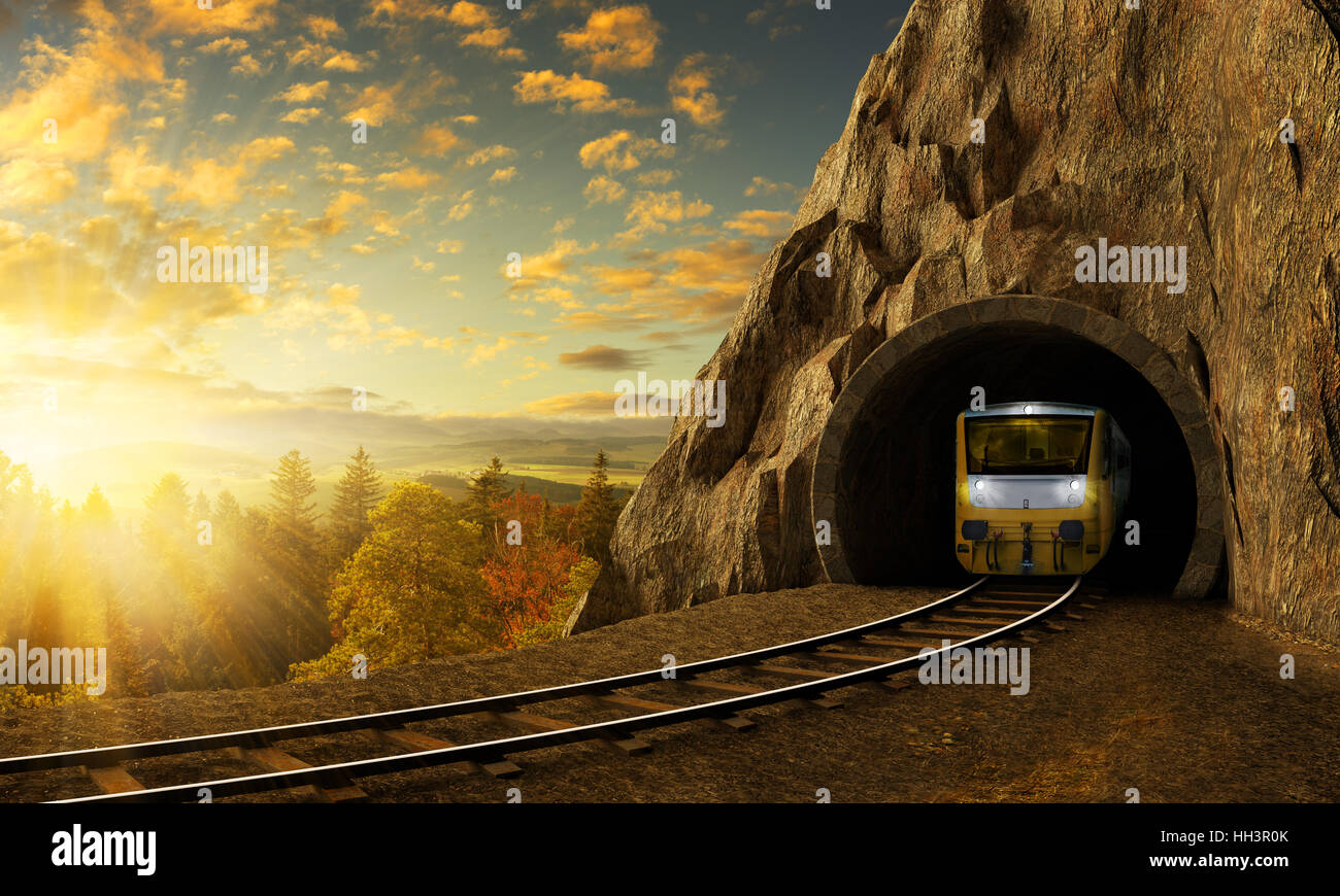 Mountain railroad with train in tunnel. Sunset landscape under the big rock. - Stock Image