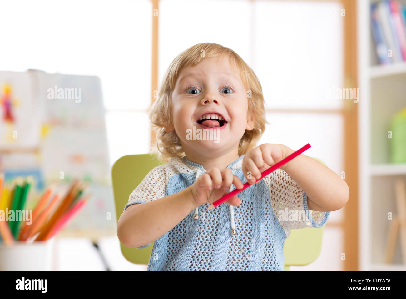 Portrait of a smiling preschool kid boy drawing - Stock Image