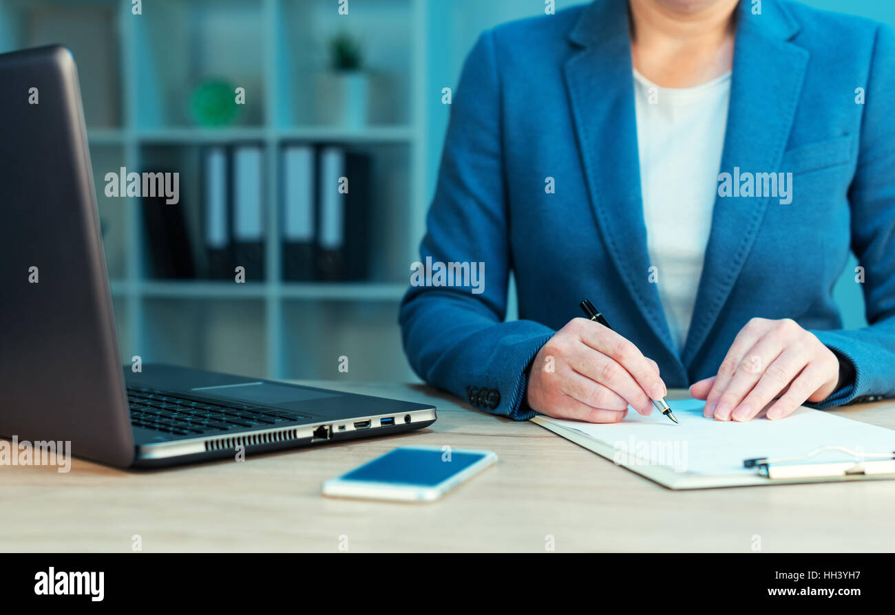 Businesswoman signing business contract agreement at office desk - Stock Image