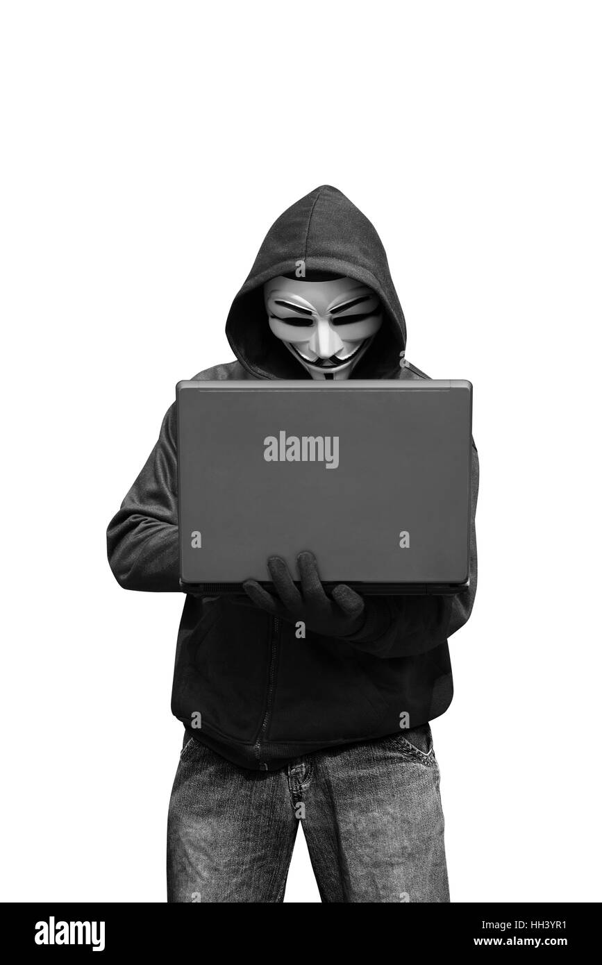 Hacker with mask holding laptop while typing isolated over white background - Stock Image