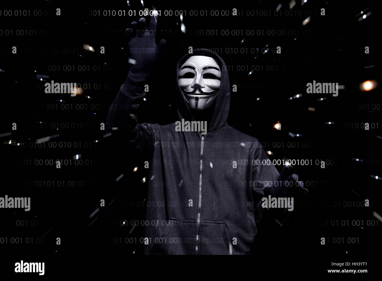Hooded man with anonymous mask hacking binary system security code on the virtual screen - Stock Image