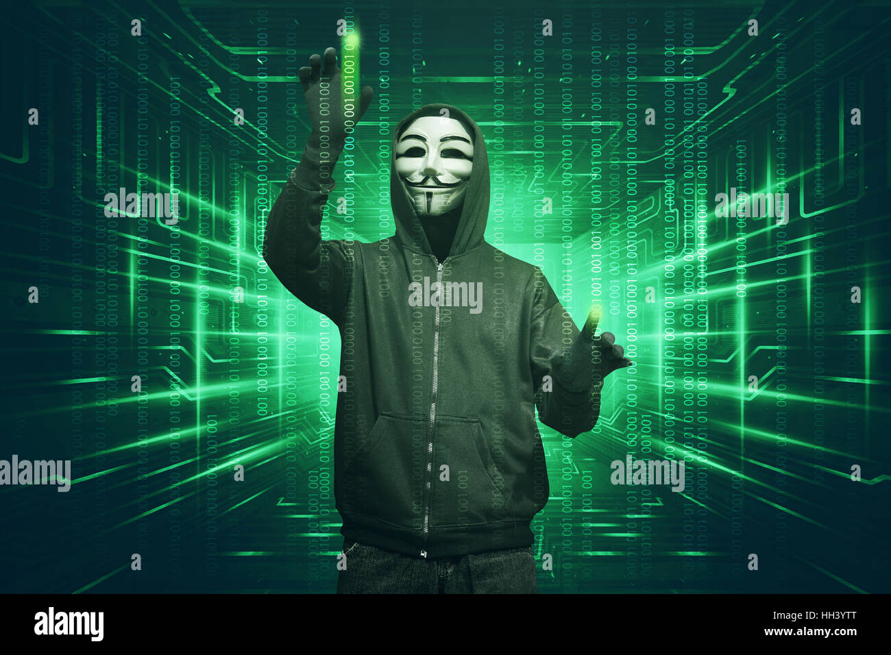 Hacker man with vendetta mask hacking binary system security code on the virtual screen - Stock Image