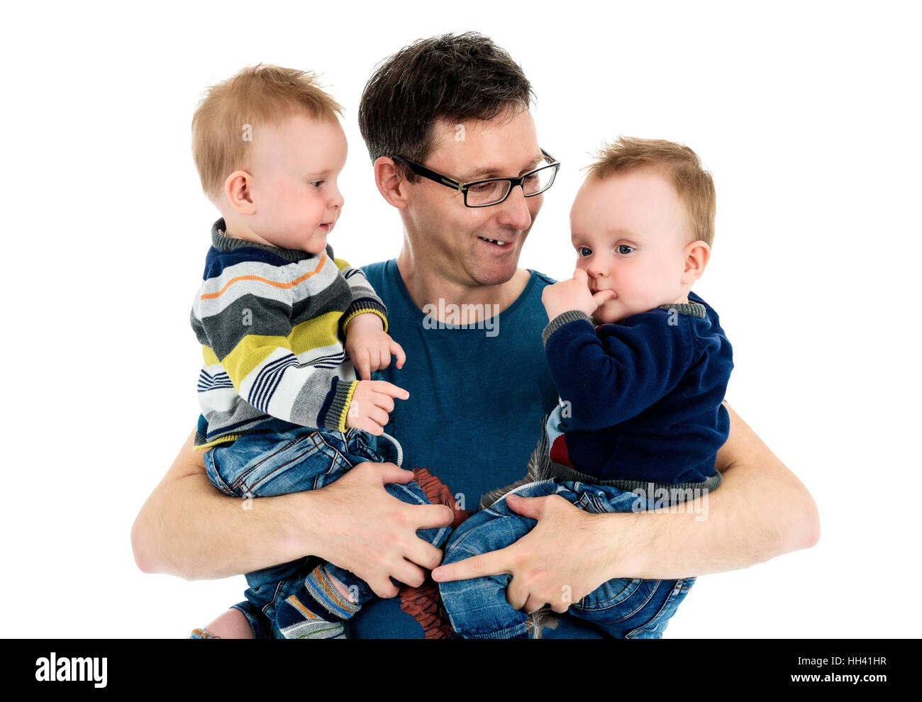 Proud Father is holding his twin sons in his arms. A single parent is carrying his twins and smiling. Isolated on - Stock Image