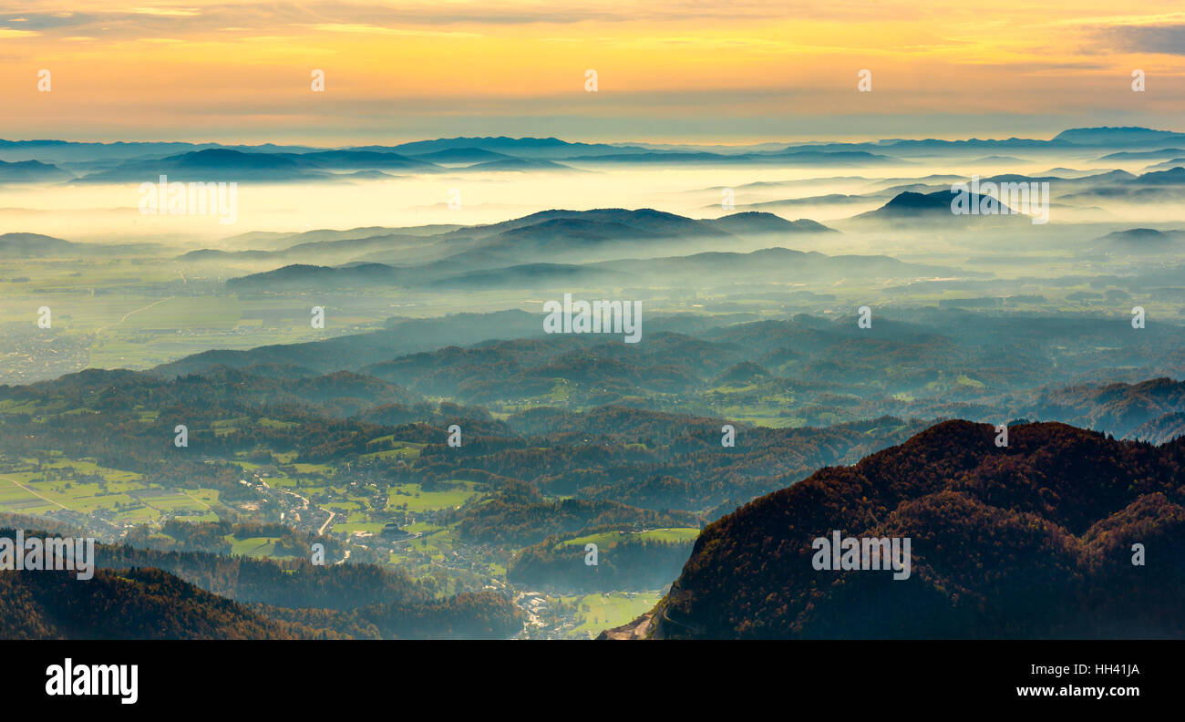 Sunset in the mountains. View of the valley. Golden hour yellow dusk or dawn with sun sunset or sunrise. Stock Photo