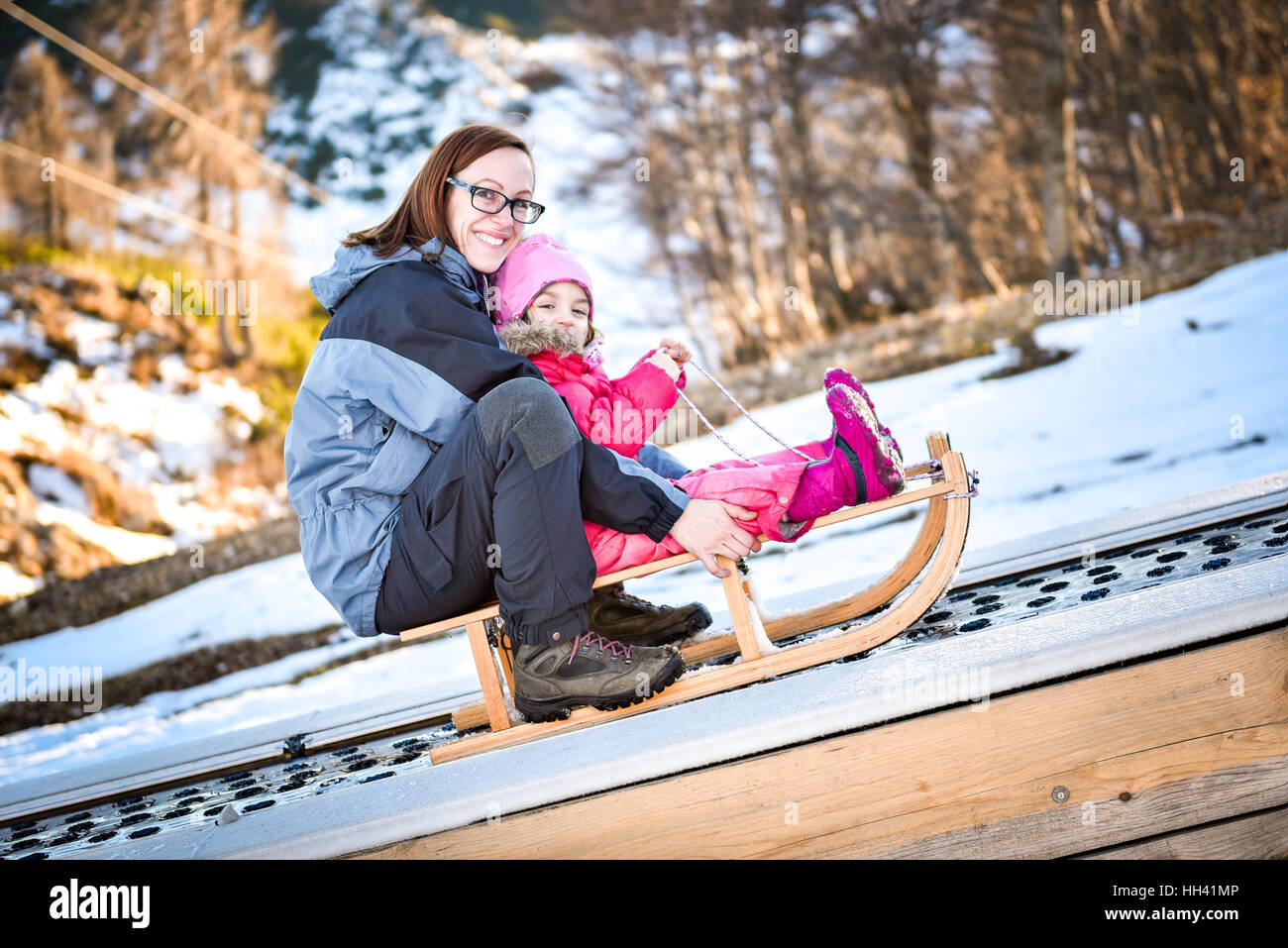 Mother and little child on a ski conveyor on sledge in ski resort school for skiing. - Stock Image