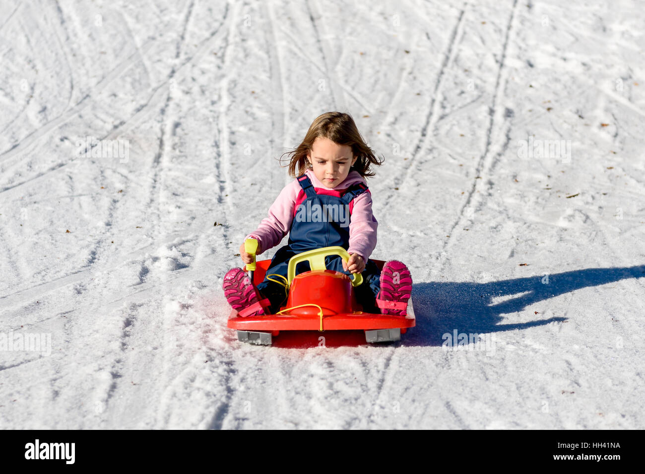 Little girl sliding with bob in the snow in wintertime. Winter vacation in the mountains with happiness concept. - Stock Image