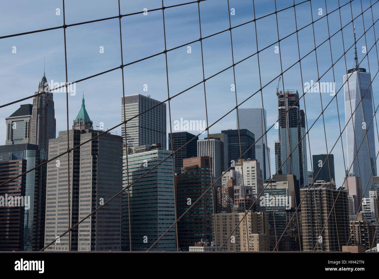 Buildings of the Financial district seen behind the arrangement of suspension ropes from Brooklyn-Bridge. Lower - Stock Image