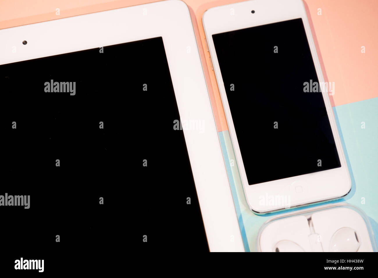 Tablet, smart phone and headphones against two-tone pink and aqua background - Stock Image