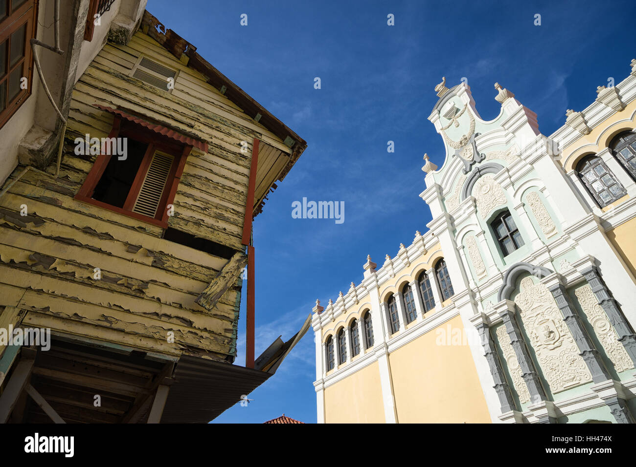 Colonial building facade newly renovated across a ruined wooden building - Stock Image